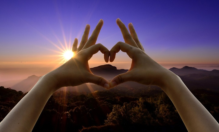 Love sign - fingers in heart shape with scenic sunset in background